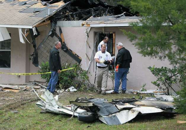 NTSB officials remove metal parts from the the scene of a plane crash on Saturday in Palm Coast, Fla. Three people were killed when a small plane crashed into a house Friday afternoon while trying to land at a central Florida airport, the Florida Highway Patrol said. Photo: AP