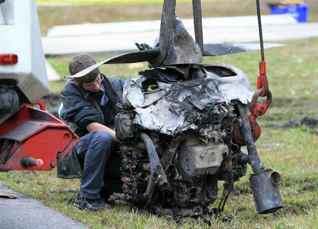 An NTSB official investigates the propeller of a plane as other wreckage and debris is removed the scene of a plane crash on Saturday in Palm Coast, Fla. Three people were killed when a small plane crashed into a house Friday afternoon while trying to land at a central Florida airport, the Florida Highway Patrol said. Photo: AP