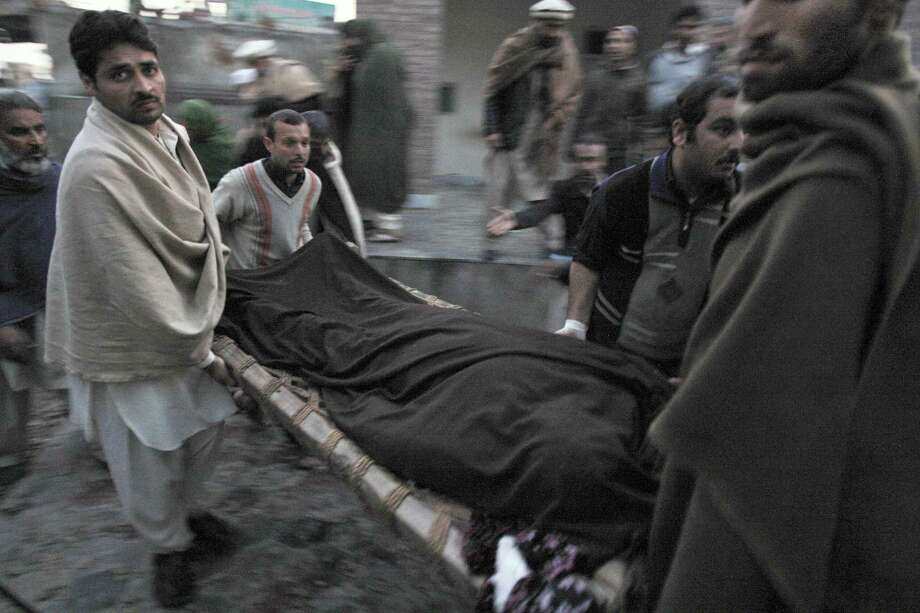 Pakistani men carry the body of a teacher, who was killed by gunmen, from a hospital for burial in Swabi, Pakistan, on Tuesday. Gunmen in northwest Pakistan killed five female teachers and two aid workers on Tuesday in an ambush on a van carrying workers home from their jobs at a community center, officials said. Photo: AP