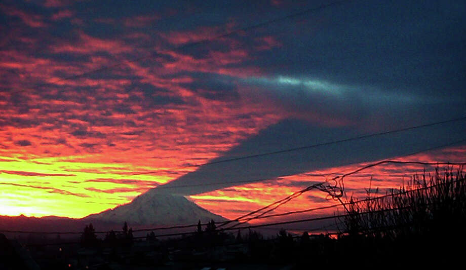 The shadow of Mount Rainier is cast by the rising sun as seen from North Tacoma the morning of New Year's Eve. Photo: AP