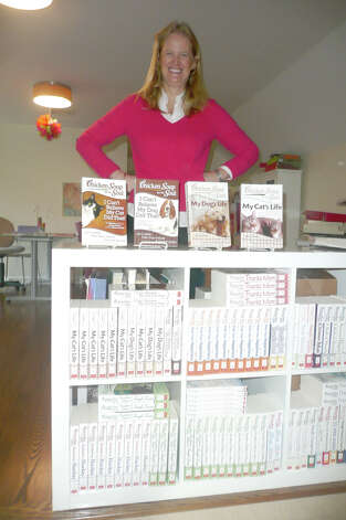 "Greenwich author Jennifer Quasha poses with some of the 14 books she has written about cats and dogs. ""I love dogs and cats!"" she says. Photo: Anne W. Semmes"