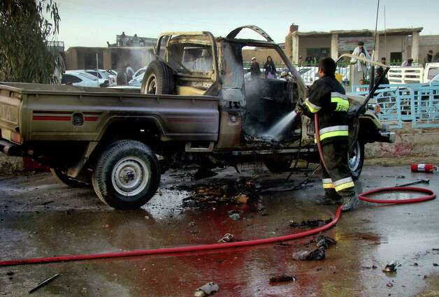 An Afghan fire fighter hoses down a damaged vehicle after a bomb blast in Lashkar Gah, Helmand province southwest of Kabul, Afghanistan, on Sunday. In neighboring Helmand province, a bomb planted at a bus station killed one policeman and wounded another person, a provincial official said. Photo: AP