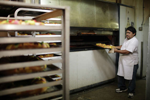 Panifico Bake Shop baker Jorge Gamero, takes Roscas de Reyes bread out of the oven, Sunday, Jan. 6, 2013. Traditionally, the bread is eaten in celebration of the arrival of the Magi during their visit with baby Jesus Christ. A tiny plastic baby Jesus is inserted in the bread and who ever gets the slice with the baby gets to host next year's celebration. El Dia de Reyes is celebrated on January 6. Photo: Jerry Lara, San Antonio Express-News / © 2012 San Antonio Express-News