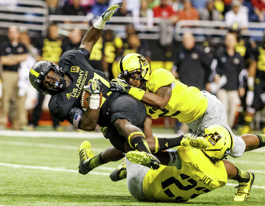 East running back Derrick Green (left) from Richmond, VA, picks up a first down while being tackled by Kameron Miles (top right) and Jack Myles during the first quarter of the 13th U.S. Army All-American Bowl at the Alamodome on Jan. 5, 2013.  The East team won the game 15-8.  MARVIN PFEIFFER/ mpfeiffer@express-news.net Photo: MARVIN PFEIFFER, Marvin Pfeiffer/ Express-News / Express-News 2012