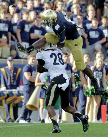 Notre Dame running back Theo Riddick leaps over Purdue cornerback Josh Johnson during the second half of an NCAA college football game in South Bend, Ind., Saturday, Sept. 8, 2012. Notre Dame defeated Purdue 20-17. (AP Photo/Michael Conroy) Photo: Michael Conroy, Associated Press / AP