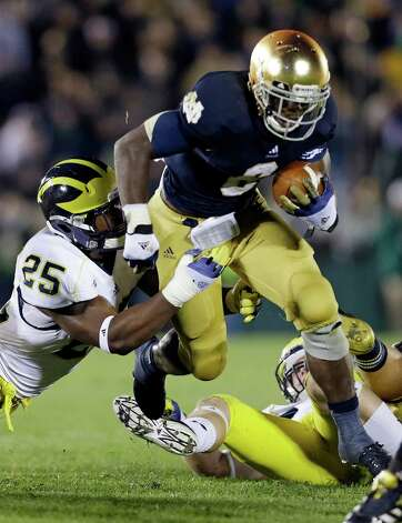 FILE - In this Sept. 22, 2012, file photo, Notre Dame's Theo Riddick (6) runs out of the attempted tackle of Michigan's Kenny Demens Photo: Darron Cummings, EN / AP