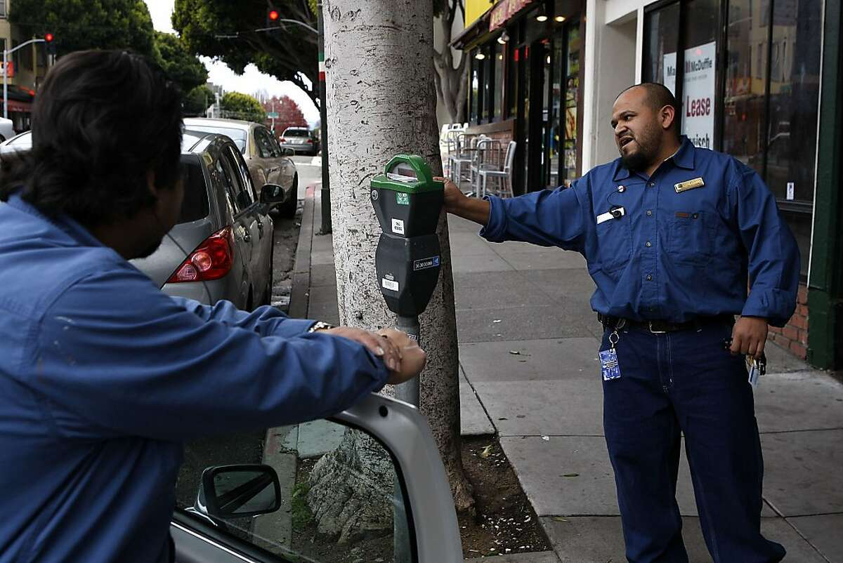 Jaime Sanchez watches on as his coworker, Agid Gonzalez, feeds a meter on Columbus Avenue on January 6, 2013 in San Francisco, Calif. Yesterday the San Francisco Municipal Transportation Agency began enforcing parking meters on Sundays.