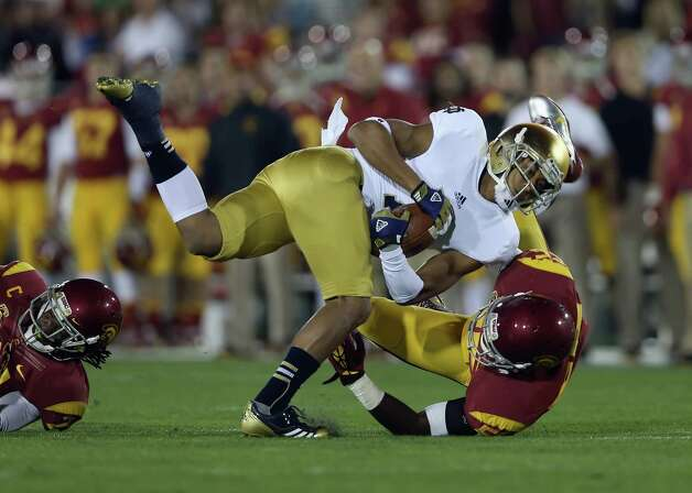Wide receiver TJ Jones #7 of the Notre Dame Fighting Irish is brought down by linebacker Lamar Dawson #55 of the USC Trojans in the first half at Los Angeles Memorial Coliseum on November 24, 2012 in Los Angeles, California. Notre Dame defeated USC Trojans 22-13. Photo: Jeff Gross, Getty Images / 2012 Getty Images