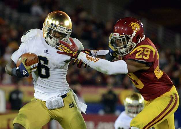 Theo Riddick #6 of the Notre Dame Fighting Irish gives Jawanza Starling #29 of the USC Trojans a stiff arm as he carries the ball during a 22-13 Notre Dame win at Los Angeles Memorial Coliseum on November 24, 2012 in Los Angeles, California. Photo: Harry How, Getty Images / 2012 Getty Images