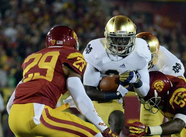 Cierre Wood #20 of the Notre Dame Fighting Irish runs with the ball as he is tackled by Jawanza Starling #29 and Lamar Dawson #55 of the USC Trojans at Los Angeles Memorial Coliseum on November 24, 2012 in Los Angeles, California. Photo: Harry How, Getty Images / 2012 Getty Images