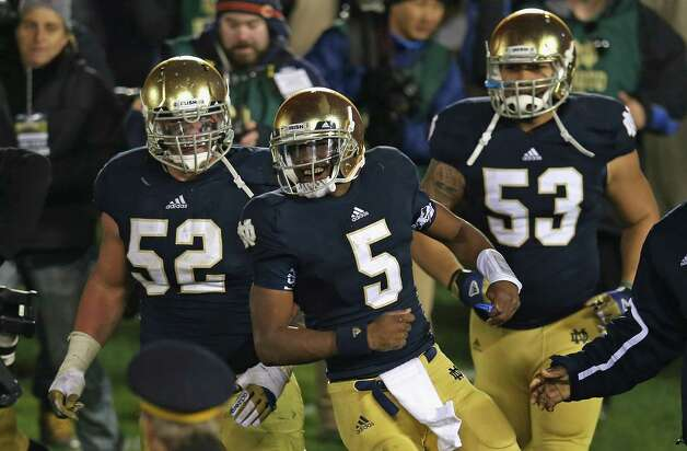 Everett Golson  #5, Braxston Cave #52 and Justin Utupo #53 of the Notre Dame Fighting Irish celebrate after Golson ran for the game-winning touchdown against the Pittsburgh Panthers at Notre Dame Stadium on November 3, 2012 in South Bend, Indiana. Notre Dame defeated Pittsburgh 29-26 in triple overtime. Photo: Jonathan Daniel, Getty Images / 2012 Getty Images