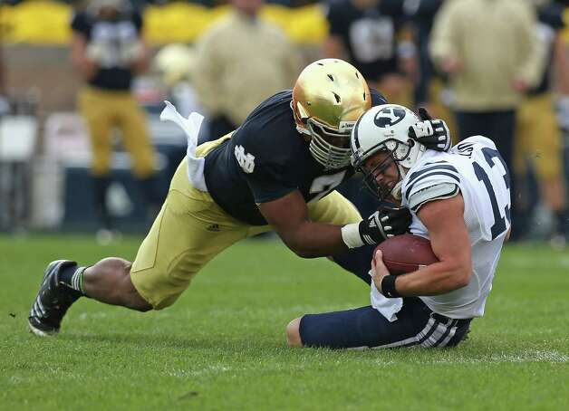 Stephon Tuitt #7 of the Notre Dame Fighting Irish sacks Riley Nelson #13 of the BYU Cougars at Notre Dame Stadium on October 20, 2012 in South Bend, Indiana. Photo: Jonathan Daniel, Getty Images / 2012 Getty Images