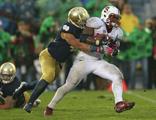 Stepfan Taylor #33 of the Stanford Cardinal is tackled for a loss by Matthias Farley #41 of the Notre Dame Fighting Irish at Notre Dame Stadium on October 13, 2012 in South Bend, Indiana. Notre Dame defeated Stanford 20-13 in overtime. Photo: Jonathan Daniel, Getty Images / 2012 Getty Images