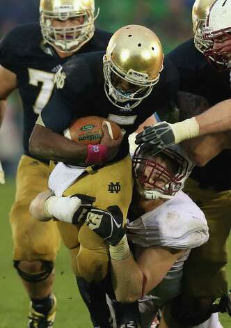 Everett Golson #5 of the Notre Dame Fighting Irish is tackled by Trent Murphy #93 of the Standford Cardinal at Notre Dame Stadium on October 13, 2012 in South Bend, Indiana. Notre Dame defeated Stanford 20-13 in overtime. Photo: Jonathan Daniel, Getty Images / 2012 Getty Images