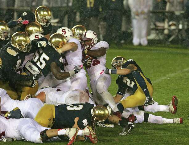 Stepfan Taylor #33 of the Stanford Cardinal is stopped short of the goal by members of the Notre Dame Fighting Irish defense on the last play of the game at Notre Dame Stadium on October 13, 2012 in South Bend, Indiana. Notre Dame defeated Stanford 20-13 in overtime. Photo: Jonathan Daniel, Getty Images / 2012 Getty Images