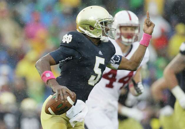 Notre Dame quarterback Everett Golson (5) runs as he looks to a pass during the first half of an NCAA college football game against Stanford in South Bend, Ind., Saturday, Oct. 13, 2012. (AP Photo/Nam Y. Huh) Photo: Nam Y. Huh, Associated Press / AP