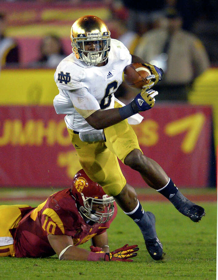 Notre Dame running back Theo Riddick, left, runs the ball as Southern California linebacker Hayes Pullard during the first half of their NCAA college football game, Saturday, Nov. 24, 2012, in Los Angeles. (AP Photo/Mark J. Terrill) Photo: Mark J. Terrill, Associated Press / AP