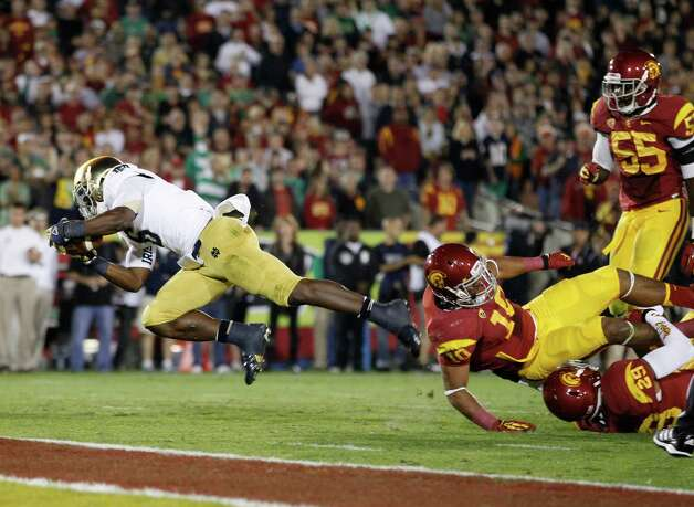 Notre Dame running back Theo Riddick, left, dives across the goal line to score a touchdown against Southern California linebacker Hayes Pullard (10), safety Jawanza Starling (29) and linebacker Lamar Dawson (55) during the first half of an NCAA college football game, Saturday, Nov. 24, 2012, in Los Angeles. (AP Photo/Danny Moloshok) Photo: Danny Moloshok, Associated Press / FR161655 AP