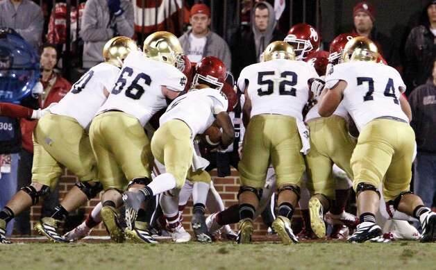 Notre Dame quarterback Everett Golson, center, dives in for a touchdown against Oklahoma during the fourth quarter of an NCAA college football game in Norman, Okla., Saturday, Oct. 27, 2012.  Notre Dame won 30-13.  (AP Photo/Alonzo Adams) Photo: Alonzo Adams, Associated Press / FR159426 AP