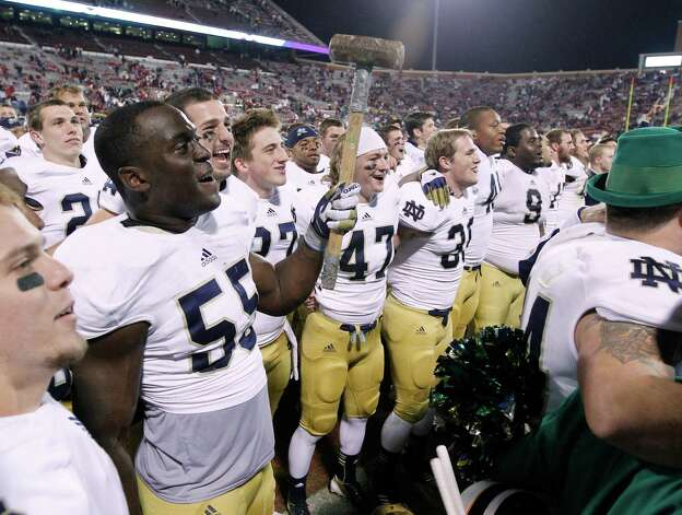 Notre Dame linebacker Prince Shembo wields a sledgehammer as he celebrates with fans following a 30-13 victory over Oklahoma in an NCAA college football game in Norman, Okla., Saturday, Oct. 27, 2012. (AP Photo/Sue Ogrocki) Photo: Sue Ogrocki, Associated Press / AP