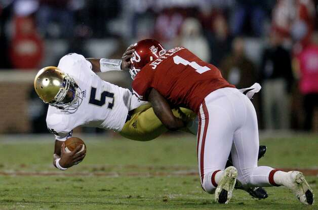 Notre Dame quarterback Everett Golson is tackled by Oklahoma defender Tony Jefferson (1) in the third quarter of an NCAA college football game in Norman, Okla., Saturday, Oct. 27, 2012. (AP Photo/Sue Ogrocki) Photo: Sue Ogrocki, Associated Press / AP
