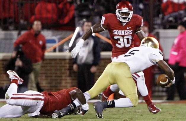 Oklahoma defensive back Gabe Lynn (9) tackles Notre Dame quarterback Everett Golson (5) during the second half of an NCAA college football game in Norman, Okla., Saturday, Oct. 27, 2012.  Notre Dame won 30-13.  (AP Photo/Alonzo Adams) Photo: Alonzo Adams, Associated Press / FR159426 AP