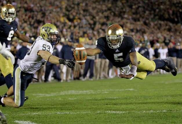 FILE - In this Nov.. 3, 2012, file photo, Notre Dame quarterback Everett Golson, right, dives into the end zone in front of Pittsburgh linebacker Joe Trebitz for a two-point conversion to tie the score late in the fourth quarter of an NCAA college football game in South Bend, Ind. Golson is doing a lot more of the little things right, and it's leading to more big plays for top-ranked Notre Dame. (AP Photo/Michael Conroy, File) Photo: Michael Conroy, Associated Press / AP