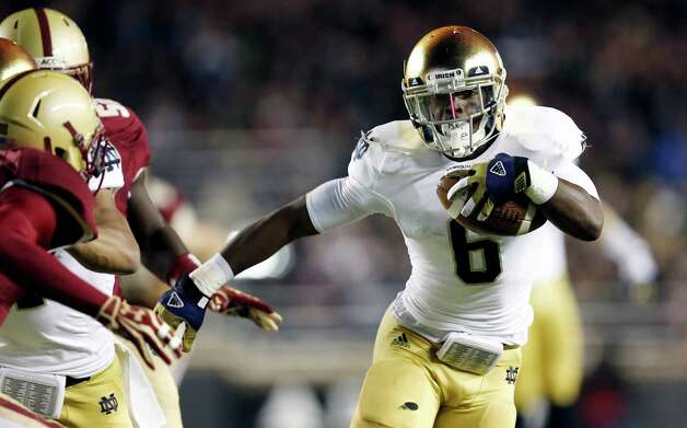 Notre Dame running back Theo Riddick breaks out past Boston College defenders during the first half of an NCAA college football game in Boston on Saturday, Nov. 10, 2012. (AP Photo/Winslow Townson) Photo: Winslow Townson, Associated Press / FR170221 AP