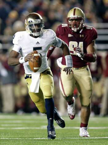 Notre Dame quarterback Everett Golson scrambles away from Boston College's Kasim Edebali during the first half of an NCAA college football game in Boston on Saturday, Nov. 10, 2012. (AP Photo/Winslow Townson) Photo: Winslow Townson, Associated Press / FR170221 AP
