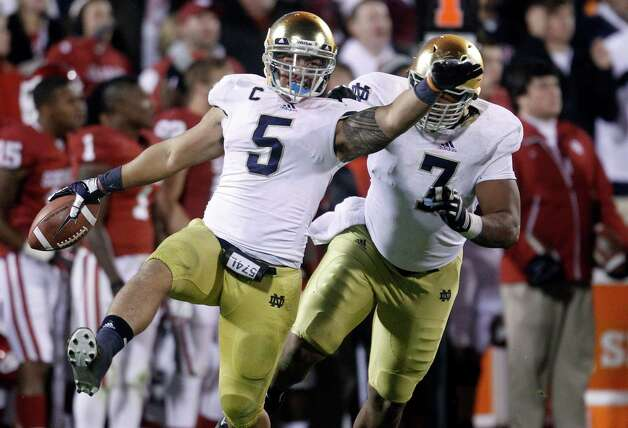 FILE - In this Oct. 27, 2012 file photo, Notre Dame linebacker Manti Te'o (5) celebrates with teammate Stephon Tuitt (7) after an interception against Oklahoma in the fourth quarter of an NCAA college football game in Norman, Okla. Te'o is a finalist for the Heisman Trophy, which will be awarded Saturday, Dec. 8, 2012, in New York. (AP Photo/Sue Ogrocki, File) Photo: Sue Ogrocki, Associated Press / AP