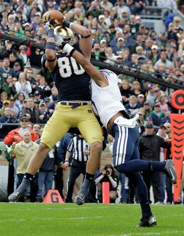 Notre Dame tight end Tyler Eifert , left, makes a catch over BYU defensive back Preston Hadley for a touchdown during the first half of an NCAA college football game in South Bend, Ind., Saturday, Oct. 20, 2012. (AP Photo/Michael Conroy) Photo: Michael Conroy, Associated Press / AP