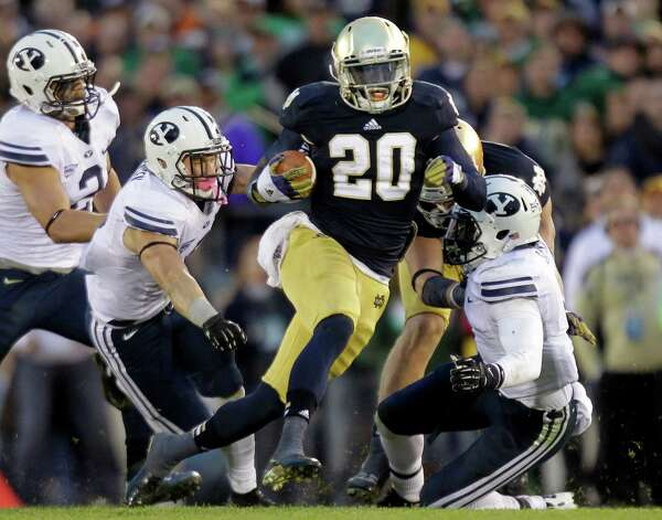 FILE - In this Oct. 20, 2012, file photo, Notre Dame running back Cierre Wood, center, cuts between Brigham Young defenders Spencer Hadley, left, Daniel Sorensen, left center, and Joe Sampson during the second half of an NCAA college football game in South Bend, Ind. Notre Dame defeated BYU 17-14.  With the national championship on the line, two throwback offenses will slug it out. No. 1 Notre Dame and No. 2 Alabama rely heavily on the run, and that doesn't figure to change in the biggest game of the year. (AP Photo/Michael Conroy, File) Photo: Michael Conroy, Associated Press / AP