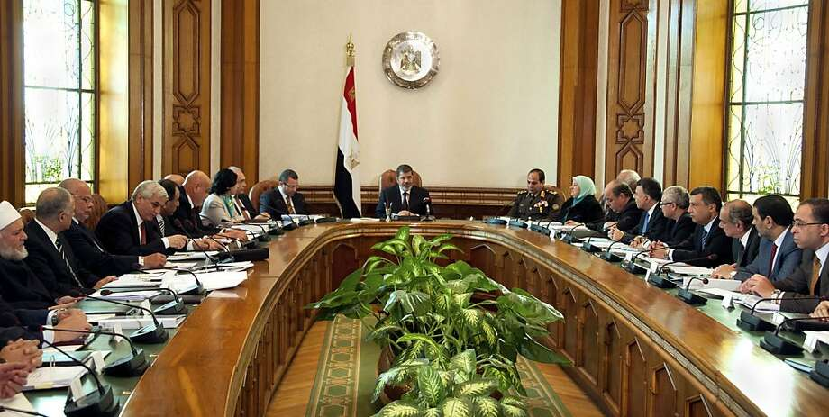 In this image released by the Egyptian Presidency, President Mohammed Morsi, center, meets with his cabinet including 10 new ministers after their swearing in at the presidential palace in Cairo, Egypt, Sunday Jan. 6, 2013. Egypt's government swore in 10 new ministers on Sunday in a Cabinet shake-up aimed at improving the government's handling of the country's struggling economy as foreign reserves levels slid closer to $15 billion, just enough to cover three months' worth of imports. (AP Photo/Egyptian Presidency) Photo: Anonymous, Associated Press