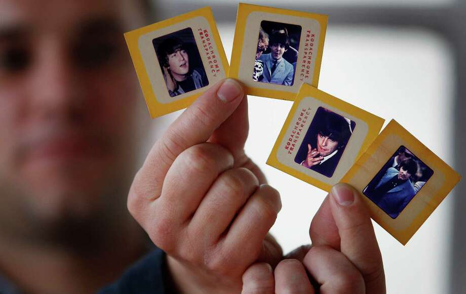 In this photo taken Dec. 29, 2012, auctioneer Paul Fairweather holds four colour transparencies of The Beatles taken during their first tour of the USA in 1964. The rare colour transparencies, taken by Dr. Robert Beck, are to be sold along with the copyright at Omega Auctions in Stockport, England, in a special Beatles memorabilia auction in March 2013. The unpublished collection of 65 slides contain many stage shots.(AP Photo/PA,Dave Thompson) UNITED KINGDOM OUT NO ARCHIVE NO SALES Photo: Dave Thompson
