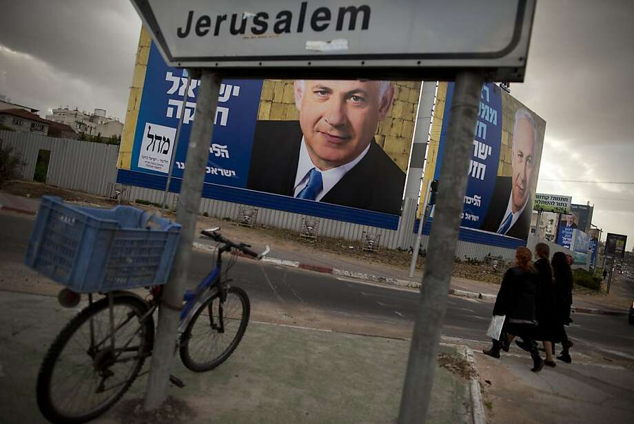 "Israelis walk past an election campaign billboard of Israeli Prime Minister and Likud Party leader Benjamin Netanyahu, in Bnei Brak, near Tel Aviv, Israel, Sunday, Jan. 6, 2013. General elections in Israel are scheduled for Jan. 22, 2013.  Hebrew on the billboards reads, "" Strong Prime Minister strong Israel."" (AP Photo/Oded Balilty) Photo: Oded Balilty, Associated Press"
