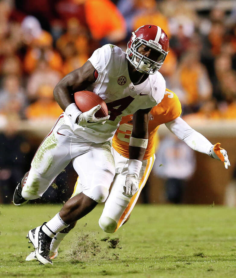 T.J. Yeldon #4 of the Alabama Crimson Tide rushes away from Byron Moore #3 of the Tennessee Volunteers at Neyland Stadium on October 20, 2012 in Knoxville, Tennessee.  (Photo by Kevin C. Cox/Getty Images) Photo: Kevin C. Cox, EN / 2012 Getty Images
