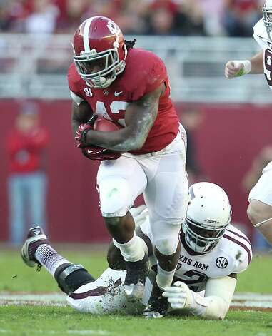 Alabama running back Eddie Lacy (42) gets brought down by Texas A&M defensive lineman Kirby Ennis (42) during the second quarter of a college football game at Bryant-Denny Stadium, Saturday, Nov. 10, 2012, in Tuscaloosa. Photo: Karen Warren, EN / © 2012  Houston Chronicle
