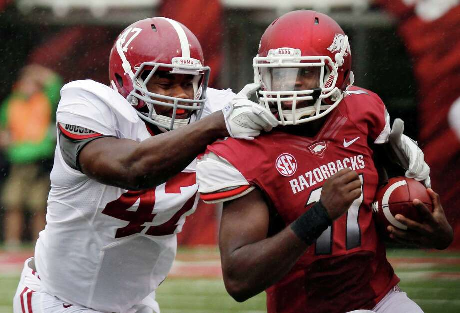 Arkansas quarterback Brandon Mitchell, right, carries against Alabama linebacker Xzavier Dickson (47) during the first quarter of an NCAA college football game in Fayetteville, Ark., Saturday, Sept. 15, 2012. (AP Photo/Danny Johnston) Photo: Danny Johnston, Associated Press / AP