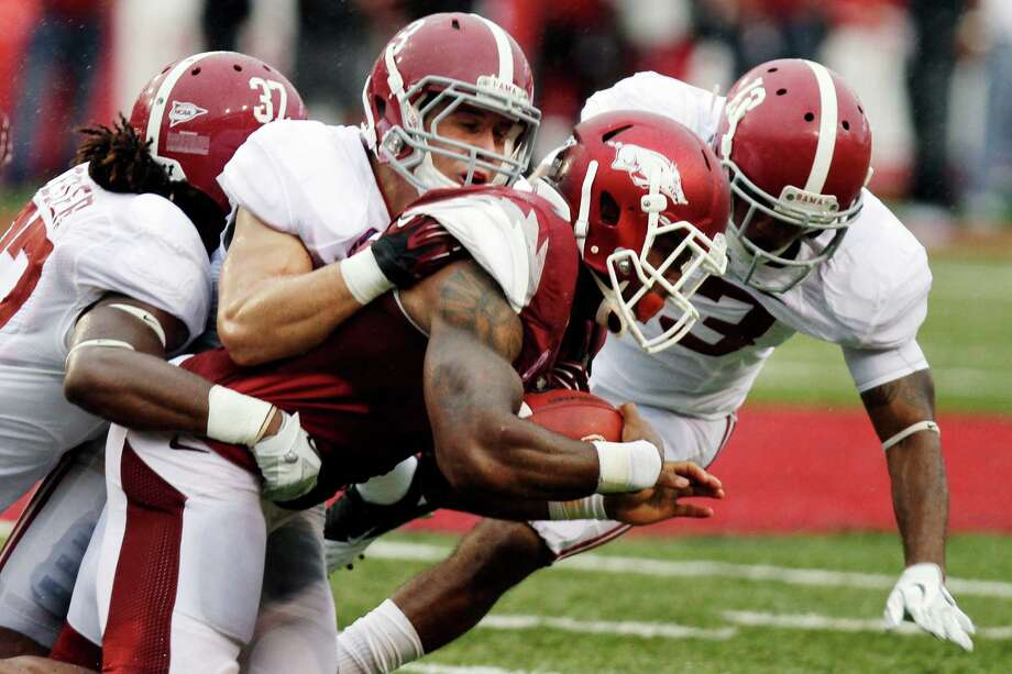 Arkansas running back Knile Davis pushes through Alabama defensive backs Robert Lester (37), Vinnie Sunseri (3) and Deion Belue, right, during the second quarter of an NCAA college football game in Fayetteville, Ark., Saturday, Sept. 15, 2012. (AP Photo/Danny Johnston) Photo: Danny Johnston, Associated Press / AP
