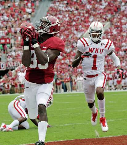 Alabama wide receiver Kevin Norwood (83) catches a first quarter touchdown pass as Western Kentucky defensive back Jonathan Dowling (1) defends in an NCAA college football game at Bryant Denny Stadium in Tuscaloosa, Ala., Saturday, Sept. 8, 2012. (AP Photo/Dave Martin) Photo: Dave Martin, Associated Press / AP