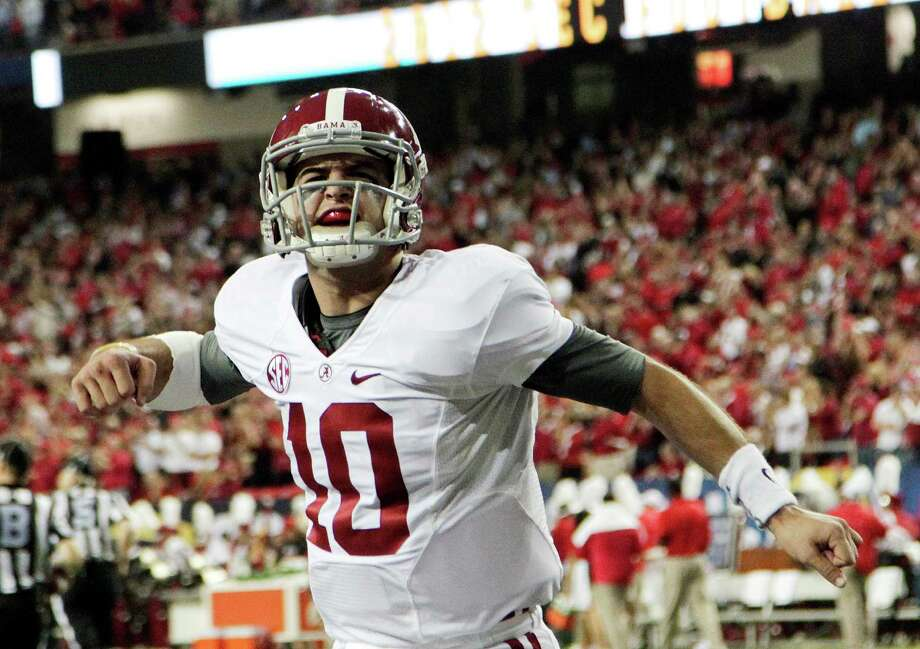 "FILE - In this Dec. 1, 2012 file photo, Alabama quarterback AJ McCarron (10) reacts after an Alabama field goal against Georgia during the first half of the Southeastern Conference championship NCAA college football game in Atlanta. The quarterback announced Thursday, Dec. 20, 2012, that he is returning for his senior season instead of entering the NFL draft. Alabama All-American linebacker C.J. Mosley also wants to graduate next December. Mosley  said "" there's lot I still haven't accomplished yet as far as football goals."" (AP Photo/Jamie Martin, file) Photo: Jamie Martin, Associated Press / FR386386"