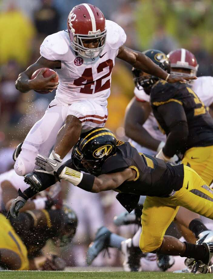 Alabama running back Eddie Lacy, top, tries to avoid Missouri defensive back E.J. Gaines while running for a short gain during the second half of an NCAA college football game Saturday, Oct. 13, 2012, in Columbia, Mo. (AP Photo/Jeff Roberson) Photo: Jeff Roberson, Associated Press / AP