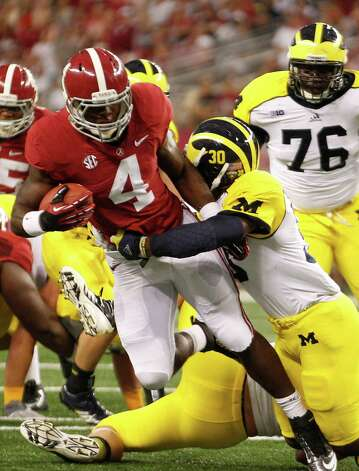 Alabama running back T.J. Yeldon (4) picks up yardage against Michigan safety Thomas Gordon (30) during the first half of an NCAA college football game at Cowboys Stadium in Arlington, Texas, Saturday, Sept. 1, 2012.  (AP Photo/LM Otero) Photo: LM Otero, Associated Press / AP