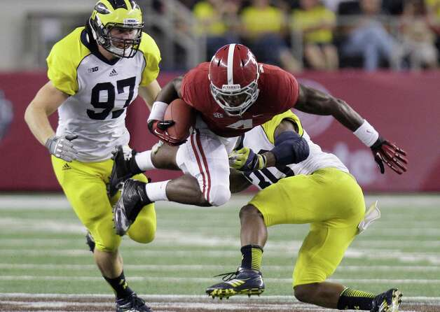 Alabama running back T.J. Yeldon (4) jumps to get extra yardage against Michigan safety Thomas Gordon (30) and defensive end Brennen Beyer (97) during the second half of their NCAA college football game at Cowboys Stadium in Arlington, Texas, Saturday, Sept. 1, 2012. Alabama  won 41-14.  (AP Photo/LM Otero) Photo: LM Otero, Associated Press / AP