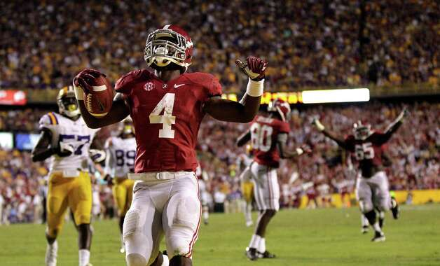 Alabama running back T.J. Yeldon (4) scores the game winning touchdown past LSU defensive end Barkevious Mingo (49) in the second half of their NCAA college football game in Baton Rouge, La., Saturday, Nov. 3, 2012. Alabama won 21-17. (AP Photo/Gerald Herbert) Photo: Gerald Herbert, Associated Press / AP