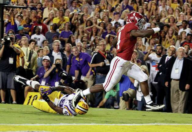 Alabama running back T.J. Yeldon (4) runs over LSU defensive end Barkevious Mingo (49) for the go ahead touchdown to beat LSU 21-17 during the second half of an NCAA college football game on Saturday, Nov. 3, 2012 in Baton Rouge, La.  (AP Photo/Butch Dill) Photo: Butch Dill, Associated Press / FR111446 AP