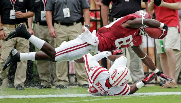 Alabama wide receiver Kevin Norwood (83) dives over the tackle of Western Kentucky defensive back Arius Wright (21) in the first quarter of an NCAA college football game at Bryant Denny Stadium in Tuscaloosa, Ala., Saturday, Sept. 8, 2012. (AP Photo/Dave Martin) Photo: Dave Martin, Associated Press / AP