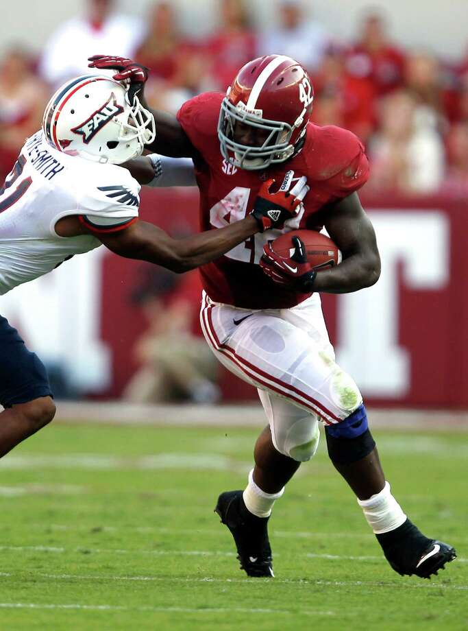 Alabama running back Eddie Lacy (42) stiff-arms Florida Atlantic defensive back D'Joun Smith (21) and runs for a first down during the first half of a NCAA college football game on Saturday, Sept. 22, 2012, in Tuscaloosa, Ala. (AP Photo/Butch Dill) Photo: Butch Dill, Associated Press / FR111446 AP
