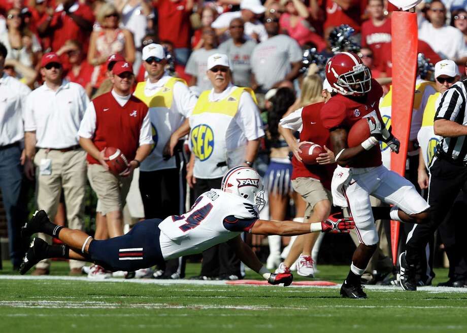 Alabama wide receiver Kenny Bell (7) gets past the out stretched hands of Florida Atlantic safety Brent Harstad (24) and runs for a touchdown during the first half of a NCAA college football game on Saturday, Sept. 22, 2012, in Tuscaloosa, Ala. (AP Photo/ Butch Dill) Photo: Butch Dill, Associated Press / FR111446 AP
