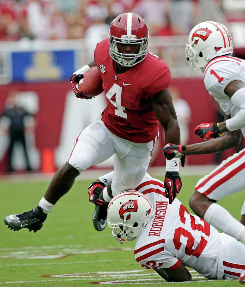Alabama running back T.J. Yeldon (4) is taken down after a first down run by Western Kentucky defensive back Tyree Robinson (22) and defensive back Jonathan Dowling (1) in the first half of an NCAA college football game at Bryant Denny Stadium in Tuscaloosa, Ala., Saturday, Sept. 8, 2012. (AP Photo/Dave Martin) Photo: Dave Martin, Associated Press / AP